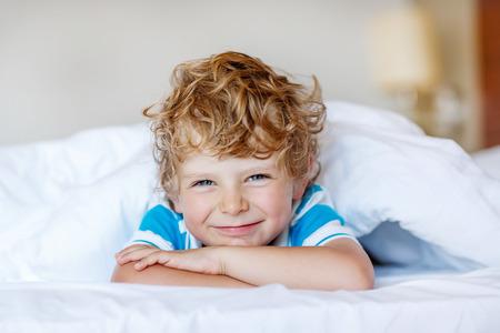後彼の白いベッドで寝ている少年は美しい幸せな子供。微笑し、笑う、室内で少し幸せな子。