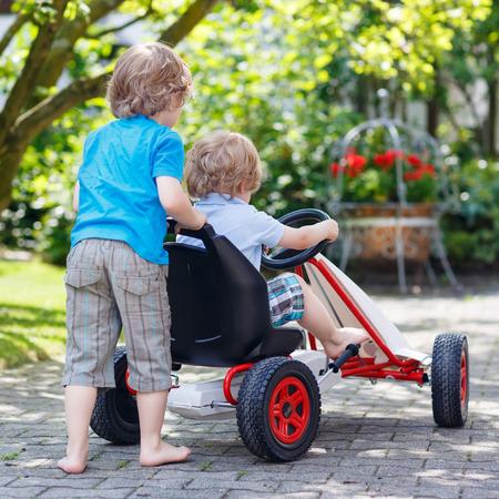 niño empujando: Dos niños de hermanos felices en divertirse con el coche de carreras de juguete en el jardín de verano, al aire libre. Adorable hermano empujando el coche con el niño más joven. Desde la parte trasera. Juegos al aire libre para los niños en verano concepto.