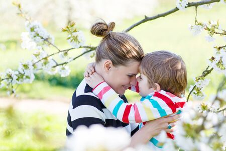 beautiful mother: Young woman and her little son, blond kid boy in blooming cherry garden in spring. Happy family enjoying nature, togetherness and celebrating mothers day.