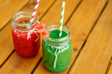 fresh spinach: Watermelon red and spinach green smoothie as healthy summer drinks. Bio organic and vegan beverage. With red watermelon hearts on skewer.