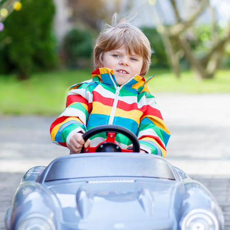 a young baby: Cute funny boy driving big toy old vintage car and having fun, outdoors. Active leisure with kids outdoors  on warm spring or autumn day. Stock Photo