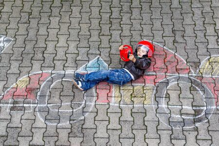 people having fun: Funny kid boy having fun with race car picture drawing with colorful chalks. Creative leisure for children outdoors in summer