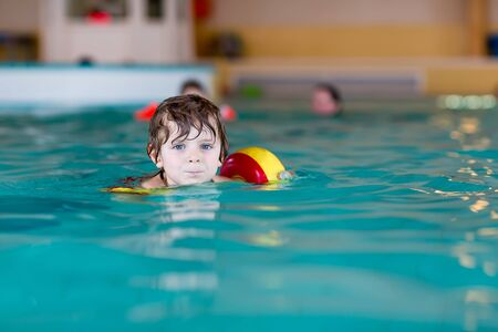 cool kids: Funny little preschool boy with swimmies learning to swim in an indoor pool. Active and fit leisure for children. Stock Photo