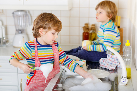 3 4 years: Two little boys of 3 and 4 years washing dishes in domestic kitchen. Children having fun with helping with housework. Indoors, siblings in colorful clothes. Selective focus Stock Photo