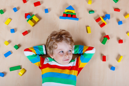 Cute blond child playing with lots of colorful wooden blocks indoor. Active kid boy wearing colorful shirt and having fun with building and creating. Stockfoto