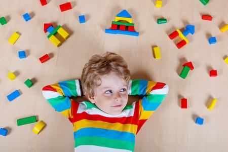 Schattig blond kind spelen met veel kleurrijke houten blokken binnen. Actieve jongen jongen dragen kleurrijke shirt en plezier maken met de bouw en het creëren.