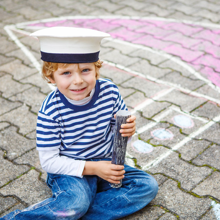 having fun: Funny little kid boy of four years having fun with ship or boat picture drawing with chalk. Creative leisure for children outdoors in summer Stock Photo