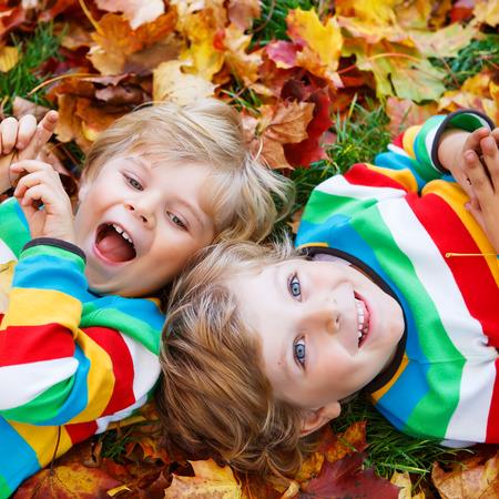 Twee kleine tweeling jongens liggen in de herfst bladeren in kleurrijke kleding. Gelukkig broers en zussen met plezier in herfst park op een warme dag. Stockfoto