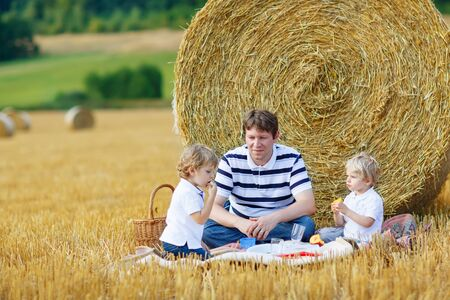 hay field: Young father and two little toddler boys having picnic on yellow hay field in summer, outdoors. Sibling kids having fun together. Family leisure.