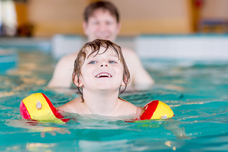 young boy in pool: Happy little kid boy and his father swimming in an indoor swimming pool. Active happy kid boy wearing safe swimmies. Family time. Stock Photo