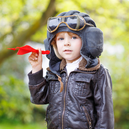pilot helmet: Happy kid boy in pilot helmet  and uniform playing with red toy airplane against green tree summer background