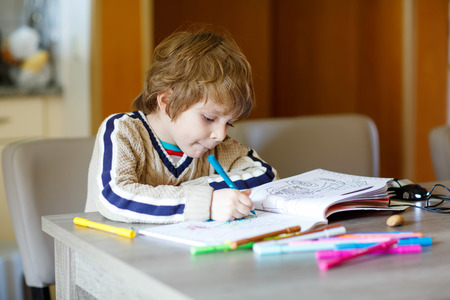 Portret van leuke gelukkige preschool jongen jongen thuis maken van huiswerk. Weinig kind schilderen met kleurrijke potloden, binnenshuis. Stockfoto