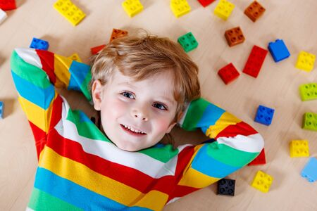 kinder: Pequeño niño rubio que juega con un montón de bloques de plástico de colores interiores. Muchacho del cabrito que desgasta la camisa de colores y divertirse con la construcción y creación. Foto de archivo