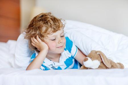 Leuke blonde jongen jongen na het slapen in zijn witte bed met speelgoed. Weinig gelukkig kind spelen met speelgoed bunny.