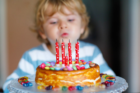 and four of the year: Adorable four year old kid celebrating his birthday and blowing candles on homemade baked cake, indoor. Birthday party for kids. Focus on cake