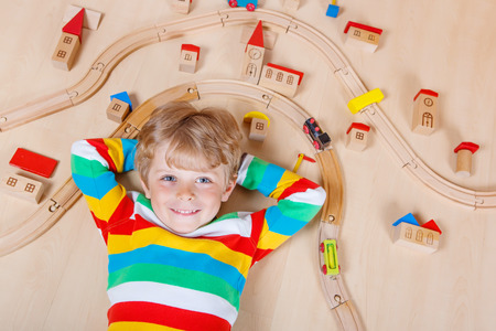 Adorable blond child  playing wooden trains and roalroad indoor. Active kid boy wearing colorful shirt and having fun with building and creating.