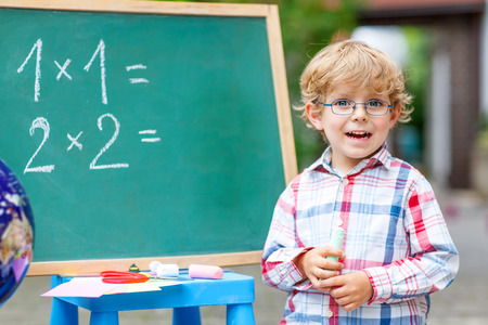 Happy funny little kid boy with glasses at blackboard practicing mathematics, outdoor. school or nursery. Back to school concept