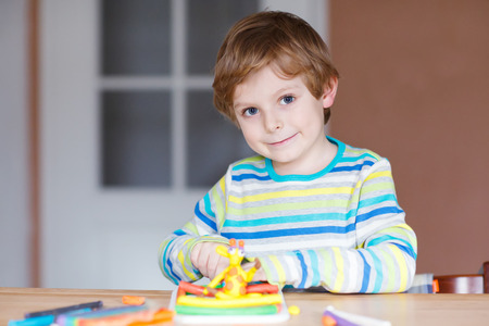 preschool boys: Smiling preschool kid boy having fun with dough, colorful modeling compound, sitting at table at home or nursery. Creative leisure with kids.