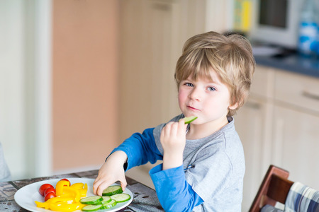 hungry children: Happy adorable kid boy eating healthy food in kindergarten or at home. Fresh vegetables as snack for children.