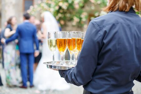 skoal: Waitress with dish of champagne and wine glasses. On outdoor wedding reception in summer.