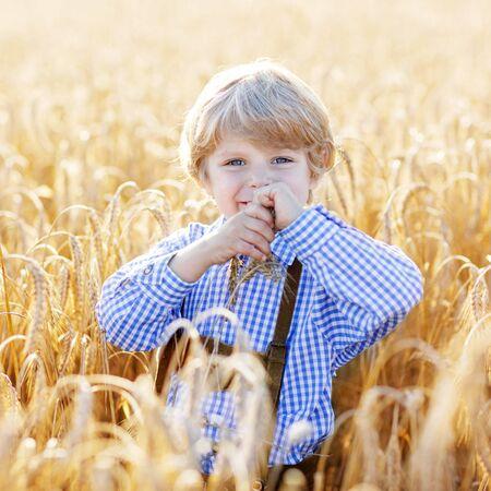comiendo pan: Divertido niño pequeño niño en ropa bávaras tradicionales alemanas, pantalones cortos de cuero y comprobar camisa, caminando alegremente a través del campo de trigo cerca de la pila de heno o paca.
