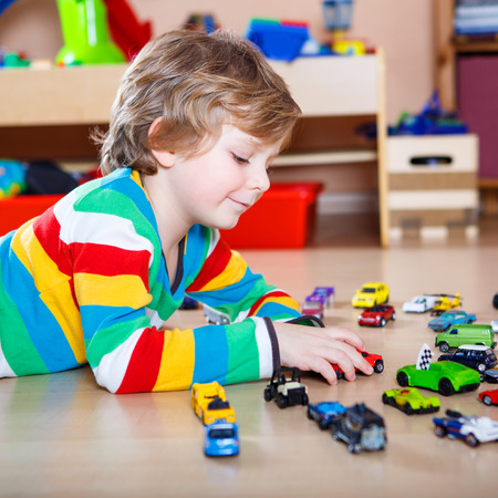 Happy funny little blond child playing with lots of toy cars indoor. Kid boy wearing colorful shirt and having fun at nursery. Stock Photo