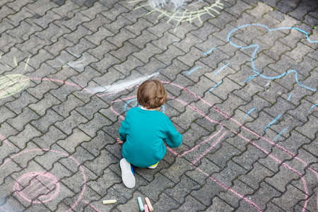 chalks: Funny  little child painting car with colorful chalks outdoors in summer. Kid having fun. Creative leisure with children outdoors.