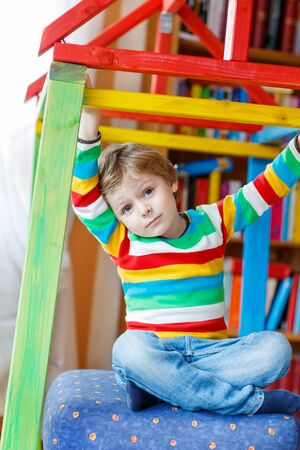 selfmade: Funny little kid boy playing in selfmade wooden colorful house. child having fun indoors. Boy wearing colorful shirt with stripes.
