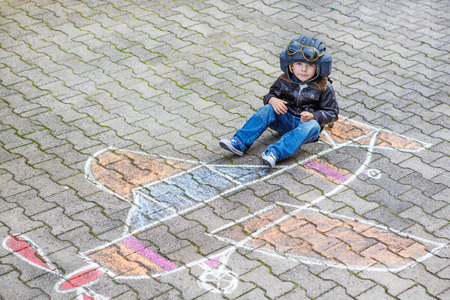 people having fun: Funny little kid boy having fun with airplane picture drawing with colorful chalk. Creative leisure for children outdoors in summer.