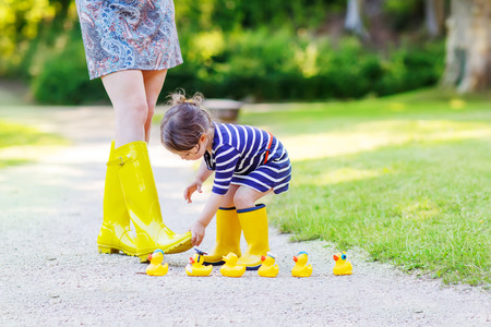 Woman and her little cute kid daughter in yellow rubber boots, family look, playing with duck toys in summer park. Active leisure with kids.