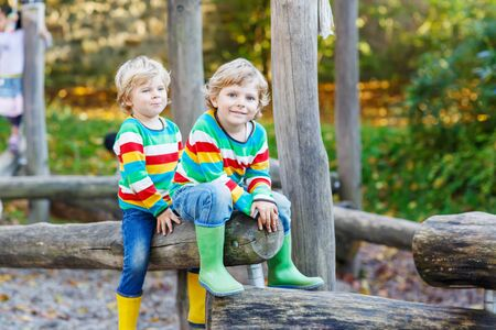 kiddies: Two little kid boys in colorful shirts with stripes and gumboots having fun with playing on playground on warm, autumn day, outdoors Stock Photo