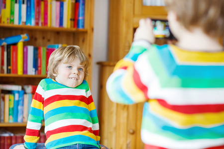 photocamera: Two little friends and kid boys making photos with photocamera, indoors. Child wearing colorful shirt. Lifestyle in a daycare or at home. Stock Photo