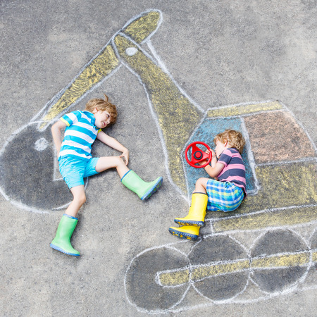 summer fun: Two little happy kid boys having fun with excavator picture drawing with colorful chalk. Creative leisure for children outdoors in summer.