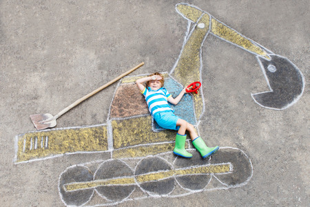people having fun: Happy funny little kid boy having fun with excavator picture drawing with colorful chalk. Creative leisure for children outdoors in summer.