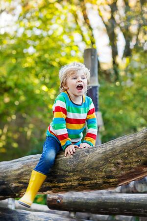 warm shirt: Little kid boy in colorful shirt with stripes and gumboots having fun with playing on playground on warm, autumn day, outdoors Stock Photo