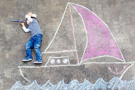 子供のための創造的なレジャー: 楽しい船またはボート描画チョークで 4 年間のおかしい男の子。 写真素材