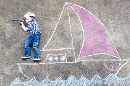 Creative leisure for children: Funny little boy of four years having fun with ship or boat picture drawing with chalk. Stock Photo