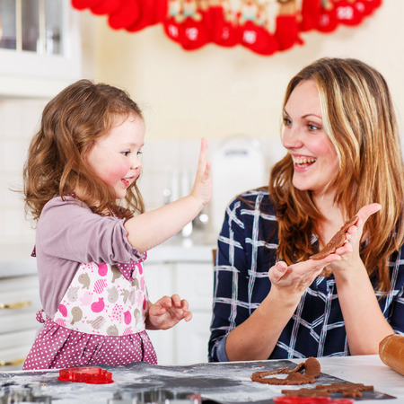 young: Happy mother, young woman in red santa hat baking christmas cookies together with her little daughter, cute blonde kid girl, sitting at the table in domestic kitchen Stock Photo
