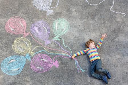 Gelukkig klein kind jongen met plezier met kleurrijke ballonnen voor foto's tekenen met kleurrijke krijtjes.