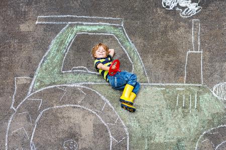 Gelukkig weinig jongen die pret met tractor foto tekenen met krijt.