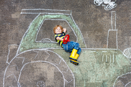 play boy: Happy little boy having fun with tractor picture drawing with chalk. Stock Photo