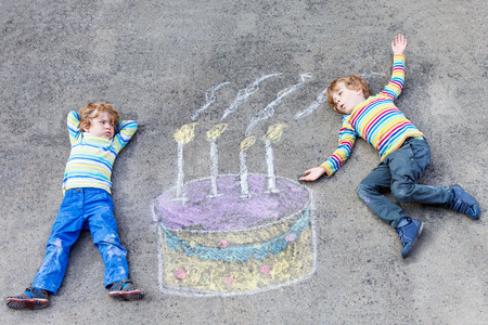 leisure: Two happy little kids having fun with big birthday cake picture drawing with colorful chalks. Creative leisure for children outdoors in summer. Kids blowing candles.