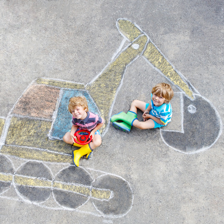 leisure: Two little happy kid boys having fun with excavator picture drawing with colorful chalk.