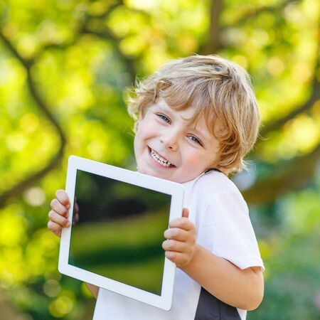 infant school: Adorable happy little child playing with gadget, outdoors. Preschool boy learning with modern technology.  Stock Photo