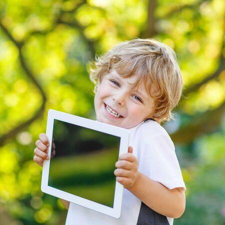 niños en la escuela: Adorable niño feliz jugando con un gadget, al aire libre. Muchacho preescolar aprendizaje con la tecnología moderna. Foto de archivo