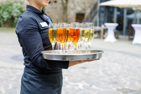 skoal: Waitress with dish of champagne and wine glasses.  Stock Photo
