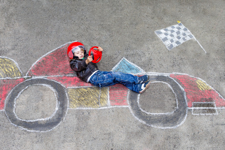races: Funny kid boy having fun with race car picture drawing with colorful chalks. Creative leisure for children outdoors in summer
