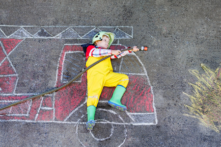 Creative leisure for kids: Little kid boy of four years having fun with fire truck picture drawing with chalk, outdoors. Dreaming of future profession. Archivio Fotografico