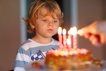 and four of the year: Adorable four year old kid celebrating his birthday and blowing candles on homemade baked cake, indoor. Birthday party for kids. Hand of adult with match Stock Photo