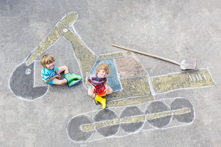 leisure: Two little happy kid boys having fun with excavator picture drawing with colorful chalk. Creative leisure for children outdoors in summer.